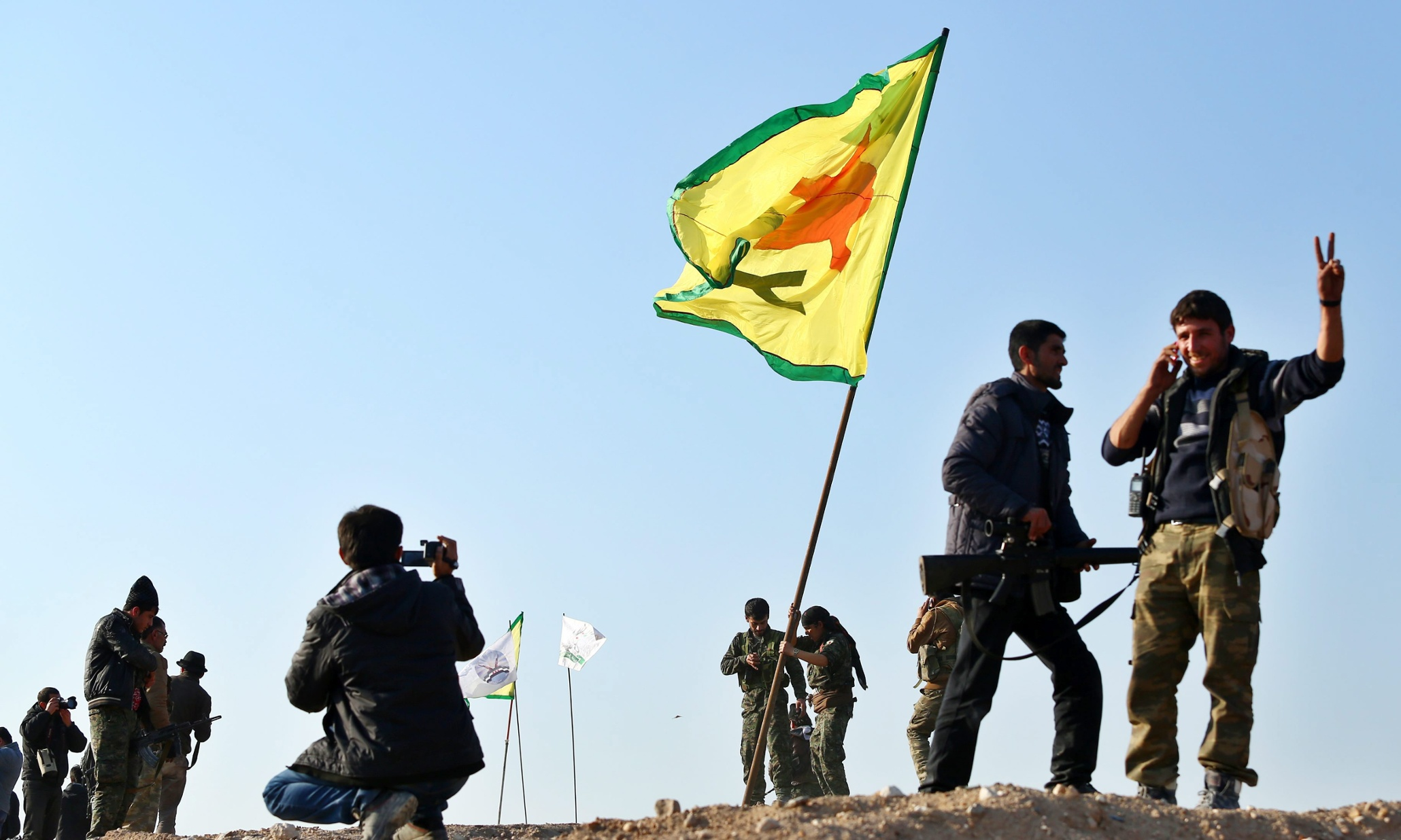 epa04586503 Members of the Syrian Kurdish People's Defence Units (YPG) celebrate their victory in Kobane, Syria, 26 January 2015. According to reports Kurdish fighters claim to have pushed militants from the group calling themselves Islamic State (IS) out of the whole of Kobane following four months of fighting, supported by airstrikes carried out by an international anti-IS coalition, though a number of the town's surrounding villages, close to the Syrian-Turkish border, remain in the hands of IS.  EPA/STR